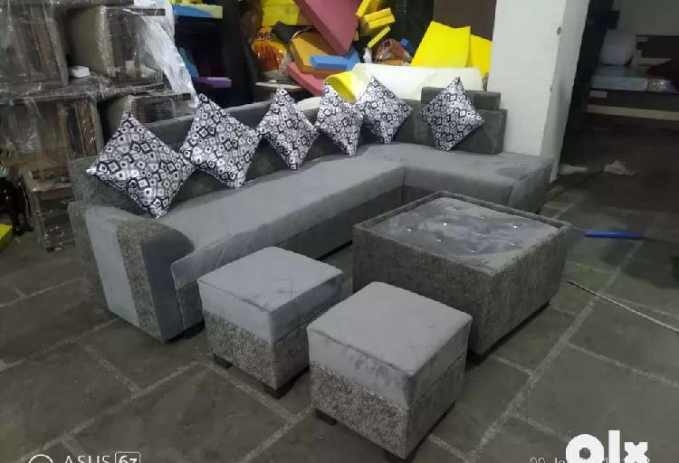 Corner sofa set with center table and puffies at satya